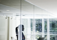 Businesswoman standing in a conference room window in a large business centre. - MINF08236