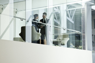 Businessman and woman standing behind a conference room window in large business centre. - MINF08245