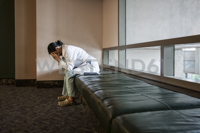 Asian woman doctor under stress sitting on a bench in a hospital. - MINF08260