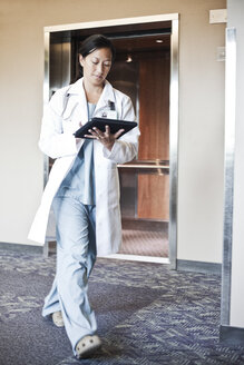 Asian woman doctor walking in a hospital hallway while working on a notebook computer. - MINF08269