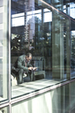 Black business man texting while sitting in front of a large widow in a lobby waiting area. - MINF08278