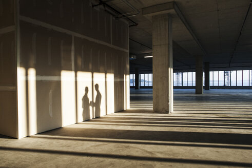 Shadows of business people cast on the sheet rock wall of a large empty raw office space. - MINF08326