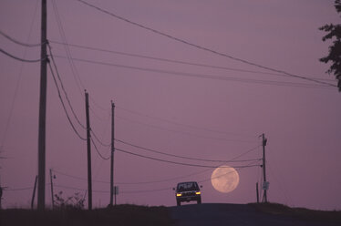 A car is seen as the moon sets at dawn and the sky begins to lighten, Maine, USA. - AURF00126
