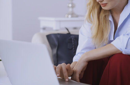 Blond woman sitting on couch, using laptop - AZF00067