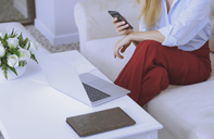 Blond woman sitting on couch, using laptop and smartphone - AZF00070