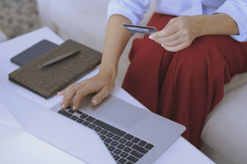 Blond woman sitting on couch, using laptop to make a payment with her credit card - AZF00073
