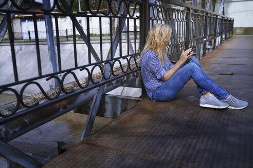 Blond woman sitting on bridge, using smartphone - AZF00079