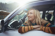 Woman sitting in car, looking at view on a road trip - AZF00082