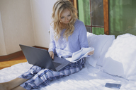 Woman sitting on bed with laptop, reading papers - AZF00094