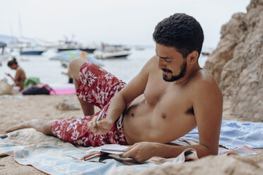 Young man at the beach, drawing in a notebook - AFVF01390