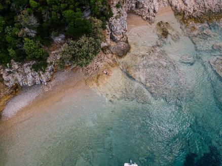 Croatia, Cres, Adriatic Sea, man lying on the rocky beach, aerial view - DAWF00708
