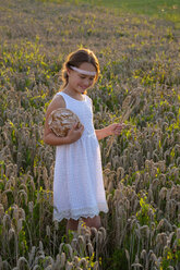 Girl standing in wheat field, holding fresh bread - LBF02018