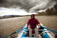 A man rafts down a rive under stormy skies in Montana. - AURF00257