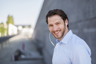 Portrait of smiling businessman wearing earbuds - DIGF04810