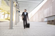 Businessman on the move pushing rolling suitcase - DIGF04828