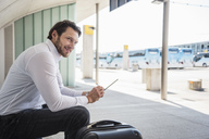 Smiling businessman with suitcase sitting at bus terminal using tablet - DIGF04849