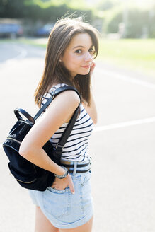 Portrait of smiling young woman with backpack outdoors in summer - GIOF04145