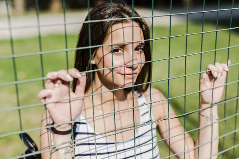 Portrait of smiling young woman behind a fence - GIOF04151