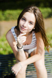 Portrait of smiling young woman sitting on a bench - GIOF04154