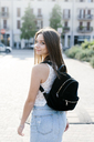 Portrait of smiling young woman with backpack in the city - GIOF04160