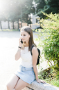 Young woman with backpack resting in a park talking on cell phone - GIOF04163