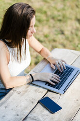 Young woman using laptop on wooden table outdoors - GIOF04169