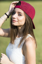 Portrait of smiling young woman wearing baseball cap outdoors - GIOF04172