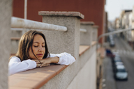 Portrait of young woman relaxing on roof terrace - AFVF01405