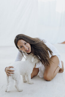Portrait of young woman having fun with dog on roof terrace - AFVF01408