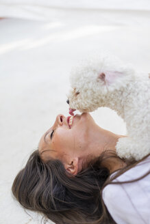 Happy young woman cuddling with dog on roof terrace - AFVF01414