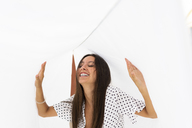 Portrait of laughing young woman  with drying bed sheets on roof terrace - AFVF01426