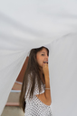 Portrait of young woman under drying bed sheet on roof terrace - AFVF01429