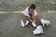 Little girl wearing pink blouse and braids tying shoes after roller skating - IGGF00505