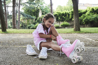 Little girl smiling at camera while putting roller skates on in the park - IGGF00508