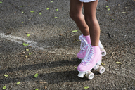 Little girl wearing pink roller blades, rollerskating - IGGF00511