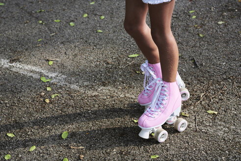 Little girl wearing pink roller blades, rollerskating - IGGF00511