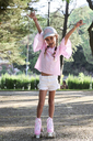 Happy little girl raising arms while roller skating in a park - IGGF00514