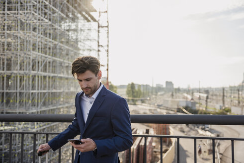 Businessman standing on bridge in the city using cell phone - DIGF04878