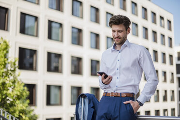 Businessman standing in the city using cell phone - DIGF04884