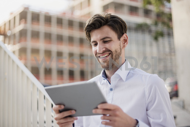 Smiling businessman in the city using tablet - DIGF04890 - Daniel Ingold/Westend61