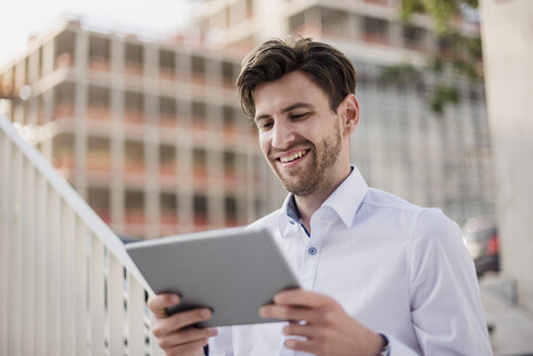 Smiling businessman in the city using tablet - DIGF04890