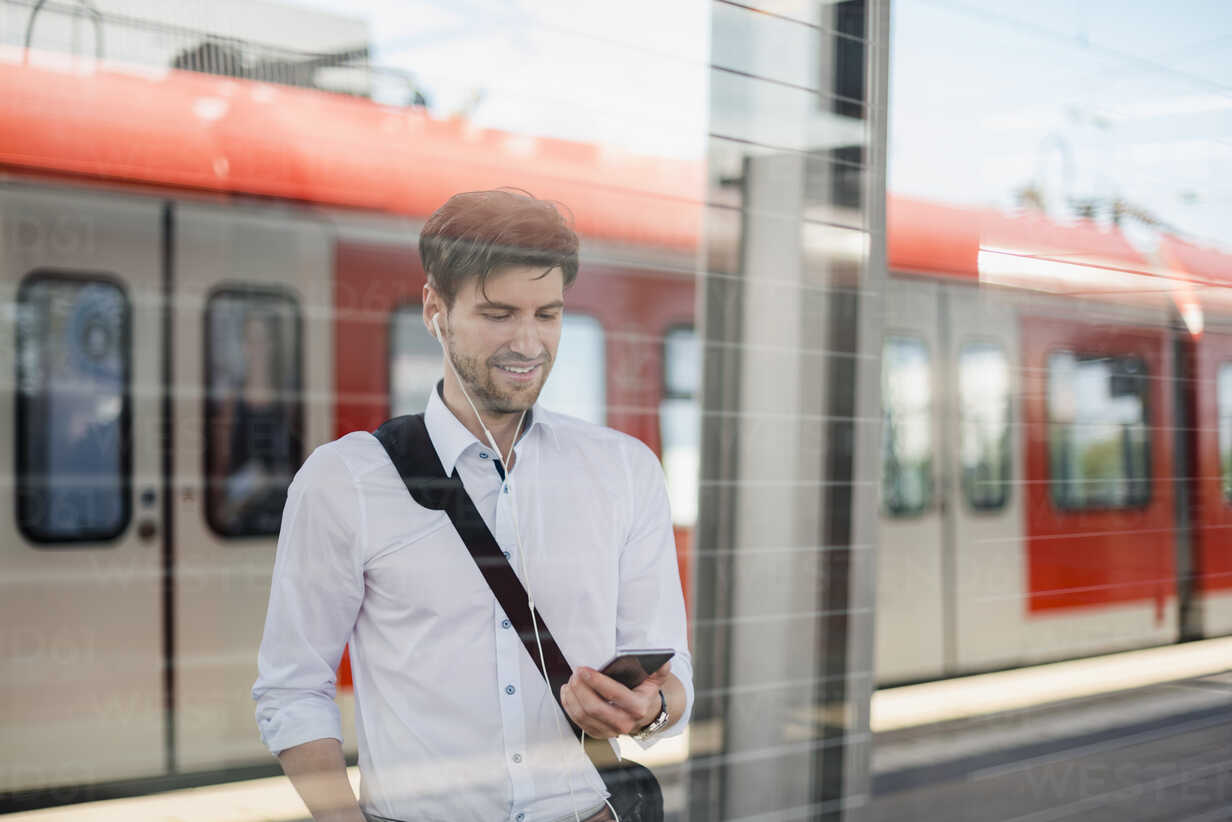 Smiling businessman on station platform with earphones and cell phone - DIGF04920 - Daniel Ingold/Westend61