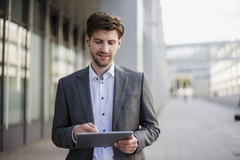 Smiling businessman in the city using tablet - DIGF04932