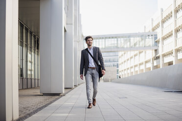 Smiling businessman with crossbody bag in the city on the move - DIGF04935