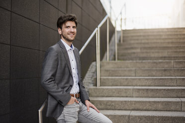 Smiling businessman standing on stairs - DIGF04938
