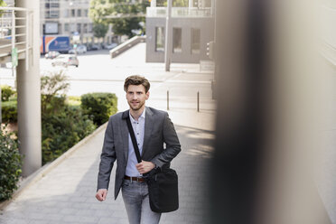 Smiling businessman with crossbody bag in the city on the move - DIGF04944