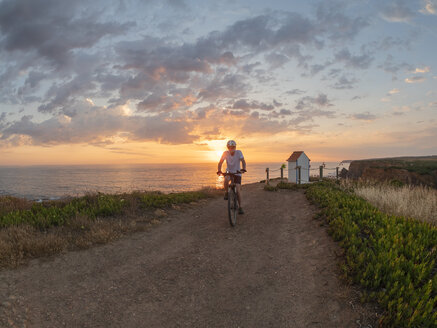 Portugal, Alentejo, senior man on e-bike at sunset - LAF02070