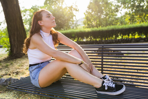 Redheaded woman sitting on bench in a park enjoying sunset - GIOF04197
