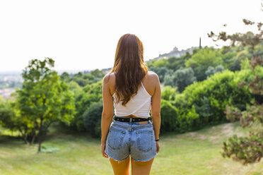 Back view of redheaded woman standing on hill in a park looking at view - GIOF04200