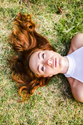 Portrait of redheaded young woman lying on a meadow - GIOF04203